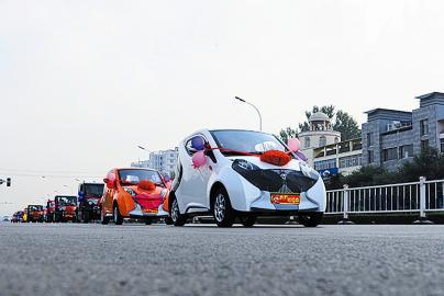6月21日,在山东省聊城市茌平县城区,一队迎亲的电动车行驶在路上.