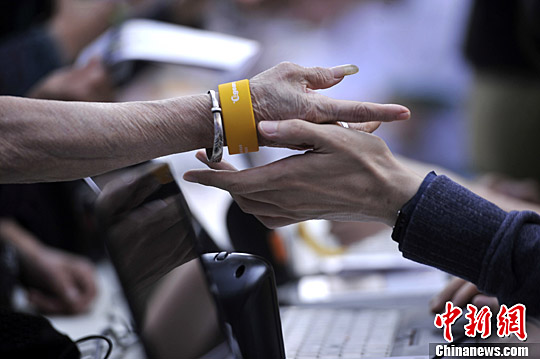 图为工作人员为老人戴上手环。陈超 摄