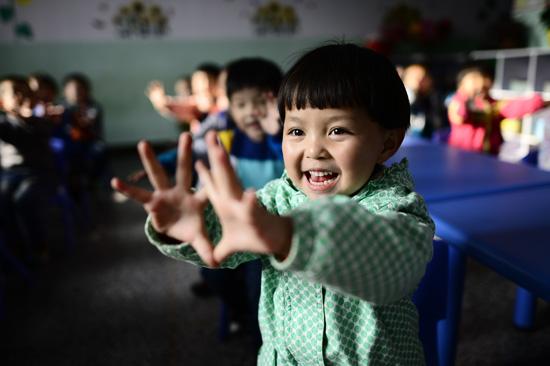 10月29日,青海省西宁市湟中县幼儿园小一班学生马熹荣和同学们一起做手指操。十二五期间,青海投入资金超过20亿元,推动基层学前教育发展,新建、改扩建公办幼儿园超过120所,对300多所民办幼儿园实施综合奖补。 新华社记者 张宏祥/摄