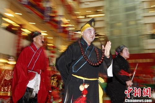 资料图 2012年2月3日,北京崇外街道元宵灯会上,市民将老北京民俗表演搬进了商场,吸引了不少观众驻足。赏花灯、舞龙、舞狮子等元宵节重要民间习俗都在此次灯会上现身。中新社记者 刘关关 摄