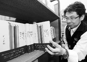 4月12日,一名日本书店的店员展示刚上架的村上春树新书。IC 图