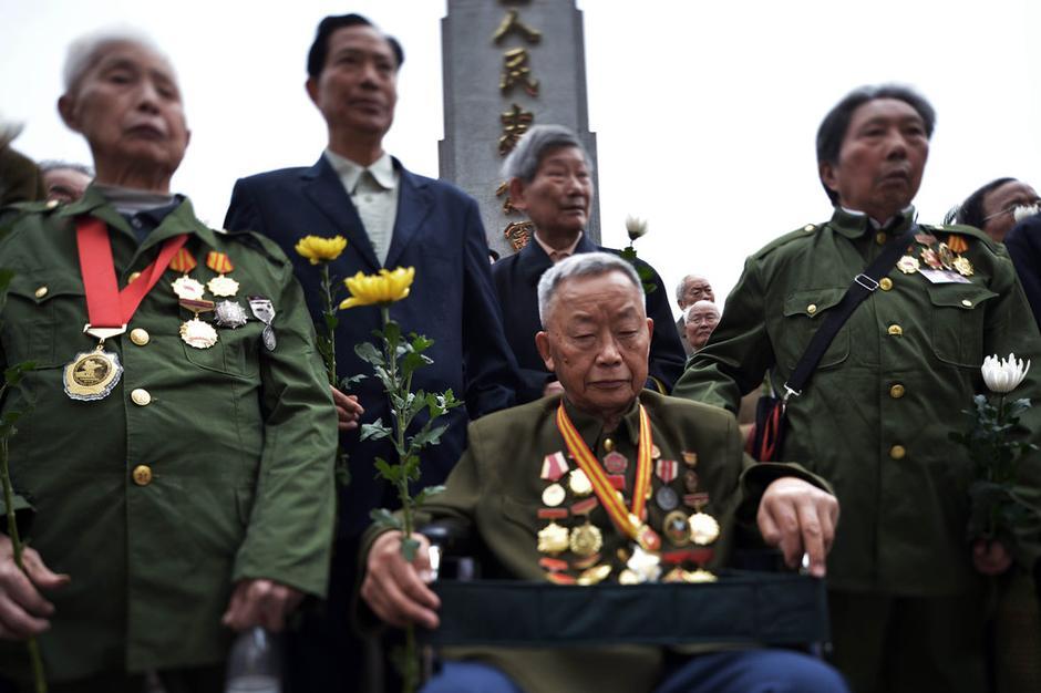 """4月2日,重庆,""""爸爸啊!你魂归故里吧!""""""""在朝鲜阵亡的战友们,你们魂归故里吧!""""……凄凉而悲壮的呼唤回荡在南岸区南山龙园军魂园,久久不散。30多位昔日抗美援朝老战士及烈士子女相聚在这里,为他们逝去的战友、父母祭奠。图为重庆南山龙园举行了纪念抗美援朝战争胜利60周年,志愿军老战士代表清明扫墓活动。"""