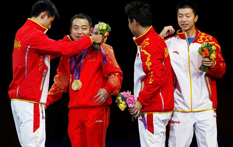 2012年8月8日,2012年伦敦奥运会男子乒乓球团体决赛,中国3-0横扫韩国,成功卫冕。图为张继科将3块金牌挂在了教练刘国梁的胸前。