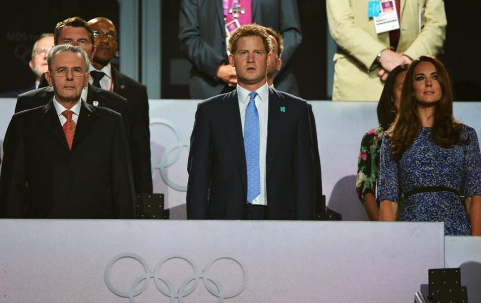 伦敦碗体育场音乐响起,刚才还喧嚣的人群突然安静下来,全场观众起立。哈里王子和国际奥委会主席罗格步入会场。巨型舞台上出现了代表英国的米字旗,英国国歌响起,负责升旗的依旧是来自陆军、皇家海军、皇家空军三军的军人。与此同时,场内演员挥舞着米字旗,全场观众高唱国歌。随着英国国旗冉冉升起,人们脸上浮现出幸福的微笑。