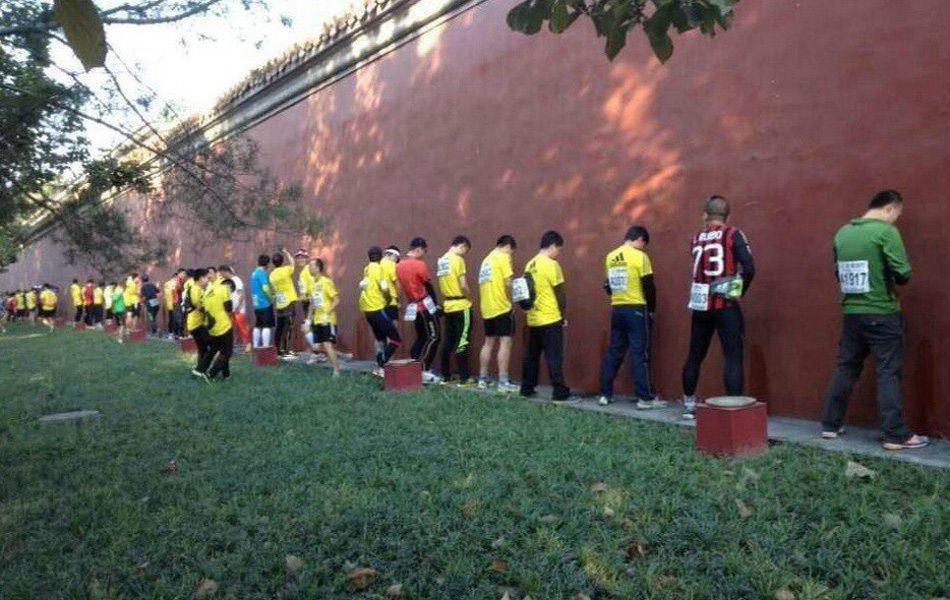 """2013年10月20日,2013年北京马拉松开赛。今年共有超过3万人报名参赛,到哪如厕成了一个焦点。一组众选手站在墙边小便照片在网上风传,选手站成一排,在沿途的红墙和绿化带""""就地解决"""",地面上""""水""""流一片。有人质疑,随处小便的原因是因为流动厕所少;也有人称,很多人就地小便是因为""""有这个传统""""。"""