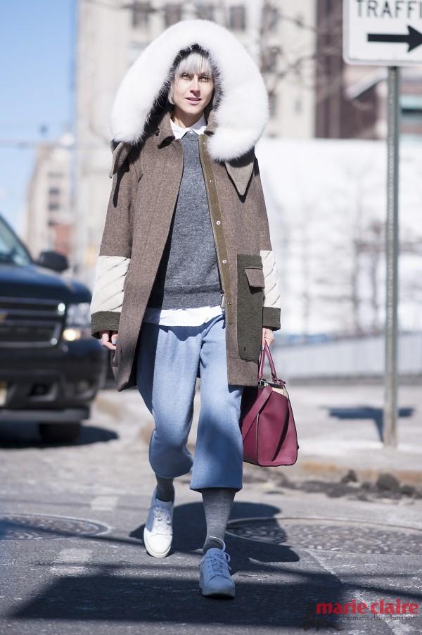 街头潮人身穿毛领大衣搭配休闲裤街拍