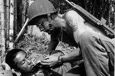 1944年3月31日 美军士兵慰问中国战友。在缅甸北部的胡康河谷,一名美军士兵弯下腰来给一名中国伤员点燃香烟。中美联军犹如两把锋利的叉子刺向日军,将敌人逐出了具有战略地位的胡康河谷。