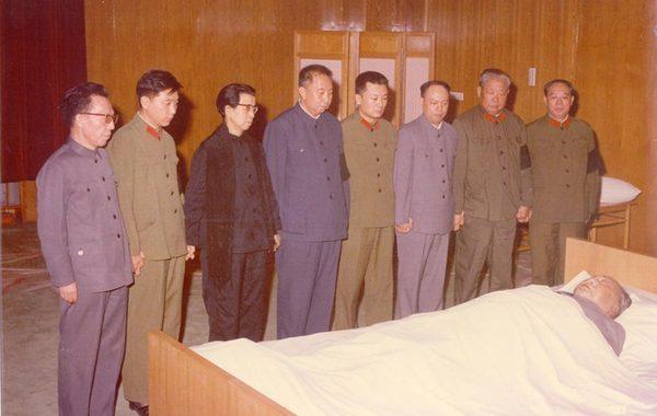 """毛泽东逝世后的头一个月内,国内政治形势变化十分微妙。眼前这张照片所显示出来的,就很说明华国锋有用心很不一般的地方,他实际上与后来被称作""""四人帮""""的几个人曾走得很近。身穿一身深蓝毛式服装的他,站在最中间,以显示自己的实际掌舵地位。他的右边的是江青。在华国锋左边站着的第一人,是毛远新。毛远新的左边是姚文元;再往左,是当时握有军权的陈锡联和毛泽东的卫队长汪东兴。江青的右边,是王洪文。最右侧站着的是张春桥。明眼人已经看出来,这八个人在刚刚逝世的毛泽东的病榻前手挽手。这里面不可言述的政治语言,足以改变后来的中国的政治走向。(来源:羊城晚报)"""