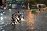 6月23日傍晚,行人在雨中艰难涉水骑车。