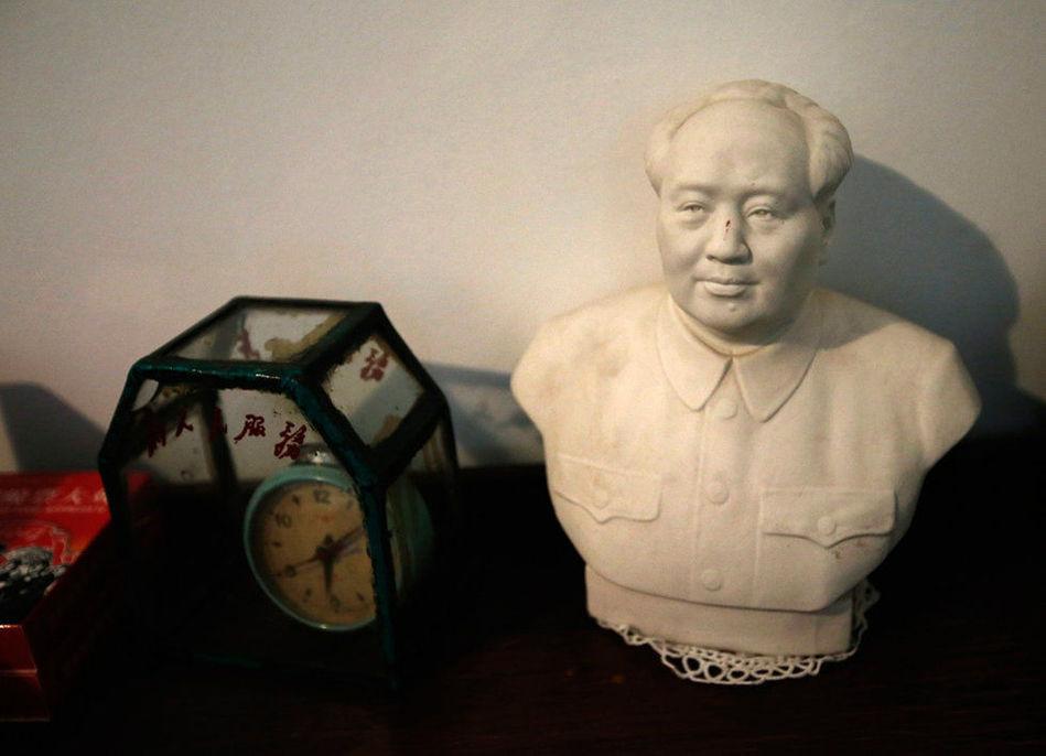 屋子一角摆放的古旧闹钟和毛主席塑像.
