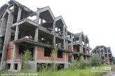 """2014年7月2日,浙江省义乌市义亭镇安居工程暨金城-香格里拉庄园""""项目,2009年开工近半年就停工,在当地政府介入下,借给开发商3300万,4栋11层的安居工程完工。但已建成三分之二的50余栋排屋一直荒废,五六年没有复工,如今已经变成一片鬼屋。"""