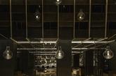 """2014年亚太区室内设计大赛获奖作品公布,由如恩设计操刀的Chi-Q获得餐饮类金奖。""""Chi""""是 kimchi 泡菜的缩写,而""""Q""""代表传统烹饪方式 barbeque 烧烤。从踏入餐厅起就有一种饶有趣味的 体验,接待处以层层木炭包覆的金属片与水泥石地点缀,灵感来自于传统韩式房屋的隐秘门厅;用餐区拥有挑高的中庭,暖色调金属天花板以独特光影与倒映式图案体现森林的轮廓;半下沉式的定制餐桌区以质朴的原木地板与镂花隔板做隔断,在韩式传统风格中糅合了潮流的精致与活力。"""