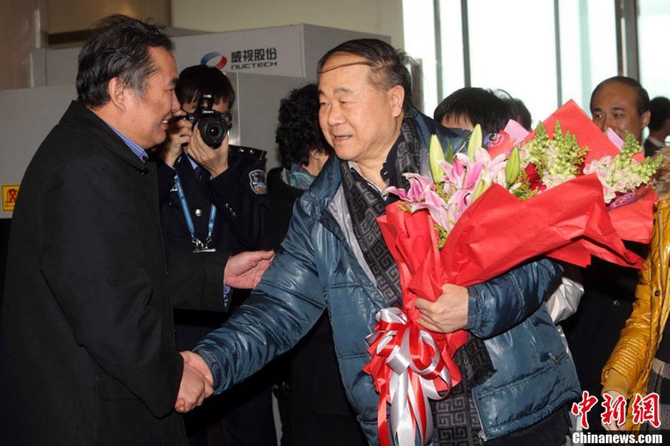 12月14日上午,2012年诺贝尔文学奖得主莫言(中)参加完颁奖典礼后乘飞机返回北京,在北京首都机场受到热烈欢迎。