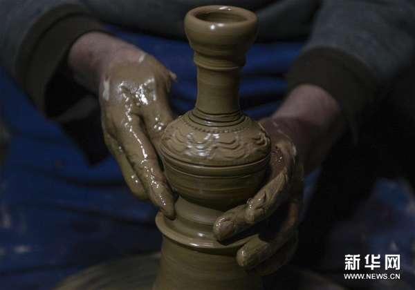 """(5)吐尔逊·肉斯坦木在作坊内制作土陶制品(12月17日摄)。 作为新疆喀什老城高台民居家族制陶的第七代传承人,64岁的匠人吐尔逊·肉斯坦木是这里最资深的手工制陶人,即便拥有常人无法掌握的技能,但吐尔逊在温度恒定方面还是无法做到精准,且因窑内受热不均,导致每炉烧制出来的土陶成品率只能维持7成左右。 2013年,年轻人祖里甫卡尔·阿巴拜克力拜吐尔逊为师,成为其家族制陶""""第八代传承人""""。与师傅不同,年轻的徒弟思维活跃,善于把维吾尔族传统乐器和"""