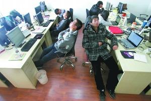 一个信息公司的员工们用餐后,靠在椅子上休息。午睡醒来的梁勇(右一)并不知道自己打呼噜。(资料图片)