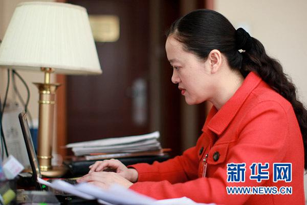 3月7日,全国人大代表何晓红在伏案写作宾馆房间修改发言稿。新华网记者 杨理光摄