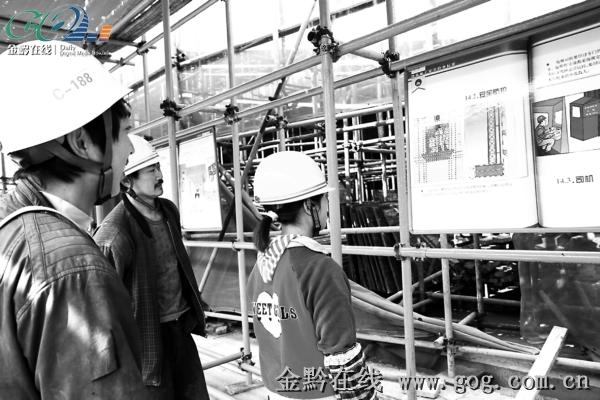 图为建筑工人在宣传展板前观看展板内容