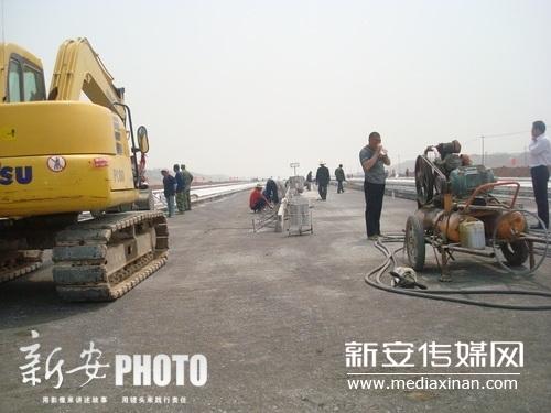 2012年4月11日上午,池州九华山机场建设工地上,工人们正在进行跑道施工。