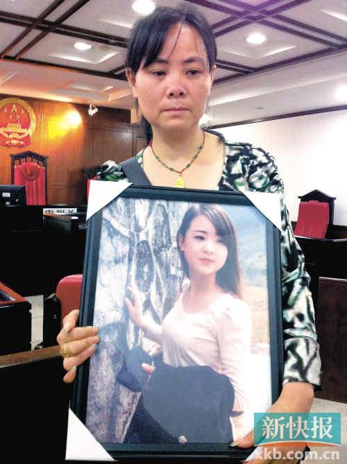 ■母亲捧着阿珍的遗照,照片可见其清新靓丽。吴笋林/摄