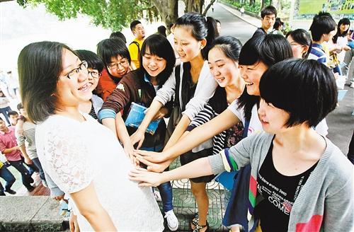 """????6月7日,重庆铁路中学高考考场,学生们轻轻摸着黄老师的肚皮,希望能沾沾""""孕""""气。 特约摄影 梅喻鑫"""