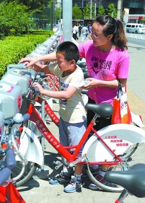 李继辉/一个孩子正和妈妈一起租用公共自行车。记者李继辉摄(来源:...