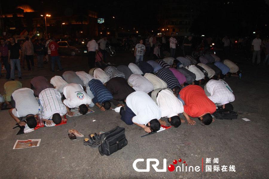 在举行游行之前,埃及民众先进行例行的礼拜活动。(方文军摄)