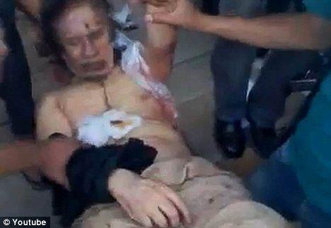 士兵把酷似卡扎菲的尸体当做玩偶一样摆弄。