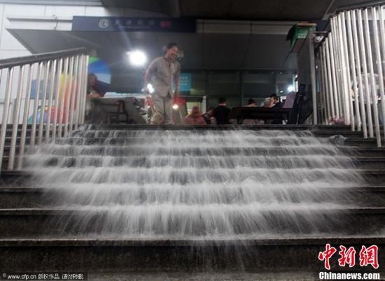 """2012年7月21日,北京突降暴雨。图为地铁工作人员排水形成""""瀑布""""。鲜康 杨登峰 摄 图片来源:CFP视觉中国"""