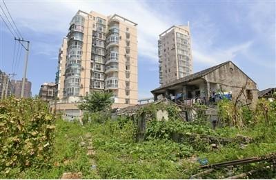 永川路改建工程地块,待拆的房屋和周边林立的高楼大厦显得格格不入.