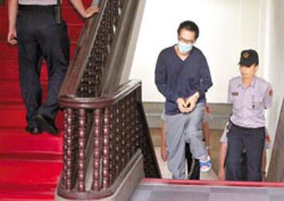 """连胜文前年""""五都""""选前之夜遭枪击案,台湾高院二审23日开庭,传唤在押的凶嫌""""马面""""林正伟(中),连胜文的委任律师当庭指林从头到尾都在说谎,法官讯后裁定还押。图片来源:台湾《中国时报》"""