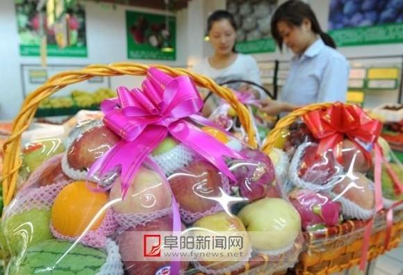 阜阳新闻网讯 中秋节和国庆节临近,近日,记者在城区一家超市看到,装有石榴、火龙果、小西瓜、苹果等水果的花篮、礼品盒摆放在柜台显著位置,购买者还可自选水果搭配水果花篮。各种水果经过了一番细致的打扮,不仅非常惹人眼,而且销量也上升了。(王彪/摄)