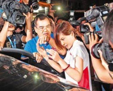 """涉贪交保的前台当局""""行政院秘书长""""林益世(左),28日晚间到松山警分局中仑派出所签到,大批媒体抢拍下,林妻彭爱佳(右)面露惊慌,林益世以手试图护住彭爱佳。图片来源:台湾《中国时报》"""