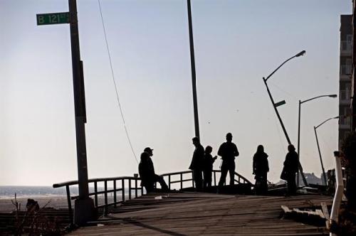 人们站在紧邻纽约皇后区的洛克威公园木板桥上,这座桥也因飓风受损。