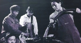 """在""""茅台名酒文化城""""的展示區內,一張名為""""茅台酒裝壇""""的照片中,一位工人正拿著一根黑色的塑料水管往壇中灌酒。 據解說員介紹,這是20世紀五六十年代的照片。 資料圖片"""