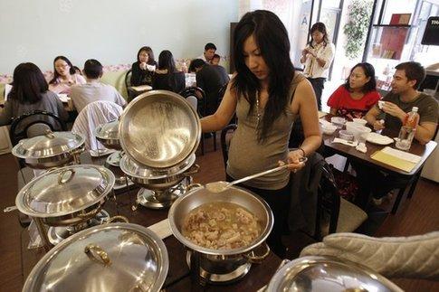 """一位華裔孕婦正在試吃""""月子餐"""" (美國僑報網援引《洛杉磯時報》)"""