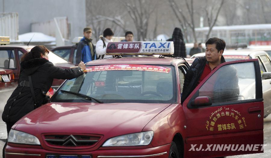 2月10日,乌鲁木齐市雷锋车队的出租车贴上统一的车标准备出发.图片
