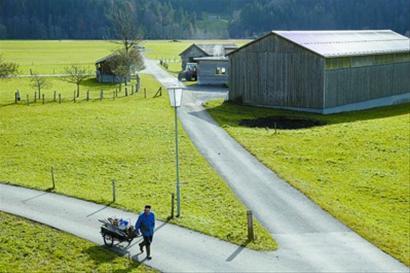 农舍外一只猫在晒太阳 王兴栋 国际周刊专稿 现在很多人都想拥有一个农舍,过上悠然的生活。没有自己的农舍,放假的时候也有不少人选择农家乐。一说到农舍,要么有的还比较原始,要么就是很现代,而要想将原始和现代和谐地融合在一起,并不容易。在奥地利西部山陵地区布雷根茨沃尔德的一个村庄,原始与高科技实现了和谐相容,同住一个村庄的既有传统的奶农,也有在该地区从事电子、服务业的蓝领白领们。而且,农舍多是木结构建筑。在推进木结构建筑所产生的碰撞中,布雷根茨沃尔德地区以时尚简约的建筑风格,巧妙地体现出绿色环保的可持续发展理