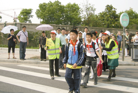 城管义工帮助小学生过马路.(资料照片)