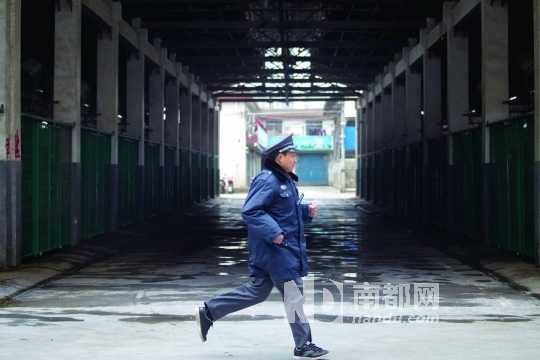2013年4月6日,上海三官堂禽蛋市场,一位保安跑过已关闭的商铺。当日,上海市暂停所有活禽市场交易,暂时关闭活禽批发交易市场,暂时禁止外来活禽进入上海。C FP
