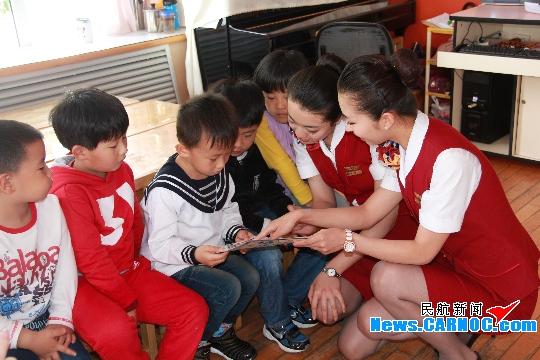 空姐们在给小朋友讲解机上《安全须知卡》 摄影:王群