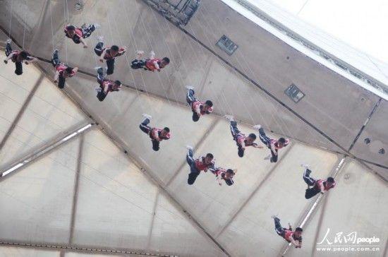 7月24日,在北京国家体育场,一群学生冒着酷暑,紧张排练。由北京市委宣传部、市旅游委主办的大型视听晚会《鸟巢吸引》将在9月12日拉开持续26场驻场演出的帷幕。其中的空中特技表演单位,是来自曾在北京奥运会开闭幕式和广州亚运会开幕式有过精彩威亚表演的河南少林寺塔沟武校。他们将在空中表演一场打斗戏,一场集艺术性、难度和规模于一体的威亚秀将呈现给中外观众。 人民网记者徐 烨摄