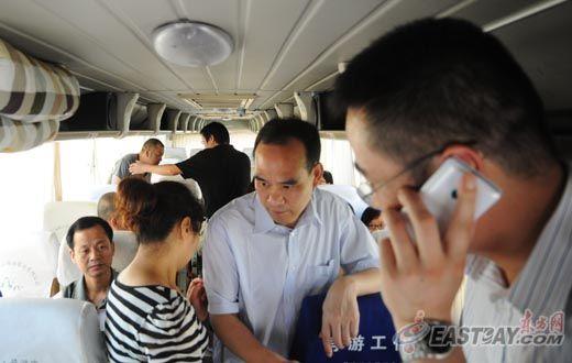图片说明:在前往上海的大巴车上,不少家长用手机与孩子保持联系。