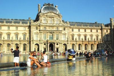 人们在卢浮宫旁边的杜乐丽花园水池边泡脚