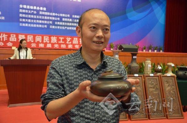 穆先生展示成功拍得的飞碟茶叶罐