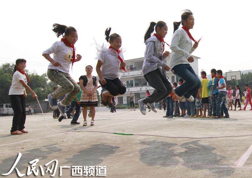 一群孩子在操场上玩跳长绳游戏