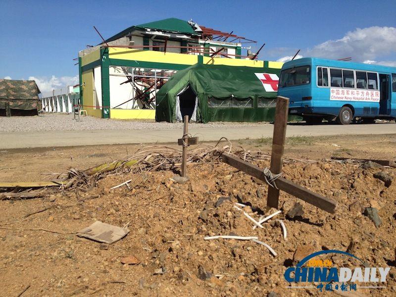 """路边时常见到被草草埋葬的遇难者坟墓。距离记者最近的就是这两具。背景里远方较小些的迷彩帐篷就是记者在灾区岸上的住所也是和平方舟医院船建在当地医院废墟上的野战医院src=""""http://y2.ifengimg.com/news_spider/dci_2013/12/39cfaa08de42e1cb1c2385dbef899e4f.jpg"""""""