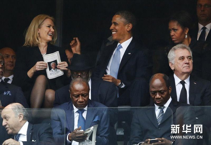 当地时间2013年12月10日,南非约翰内斯堡索韦托,曼德拉官方追悼会,奥巴马与丹麦首相赫勒·托宁-施密特交谈甚欢,而奥巴马的妻子米歇尔在一旁脸色难看。图片来源:东方IC