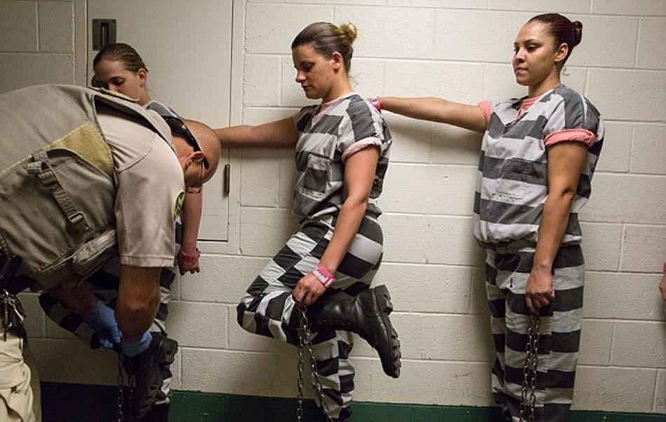 女囚们抬起脚,等待着狱警给自己戴上脚镣-外媒揭秘美国女子重囚监图片