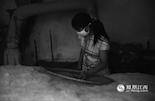 弹松了棉花,开始用竹筛压平,确保每一团棉花都弹松了,并且没有散落。这样做也可以让弹松的棉花更紧凑,不留空隙才能更保暖。