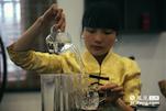 在遂川县城的第一边,一家茶企里,来自于赣州定南的徐灵微在向客人们展示狗牯脑的泡茶技艺。由于狗牯脑的鲜嫩特点,必须要使用80度左右的水进行冲泡,所以在泡茶前多了一个凉水的环节。